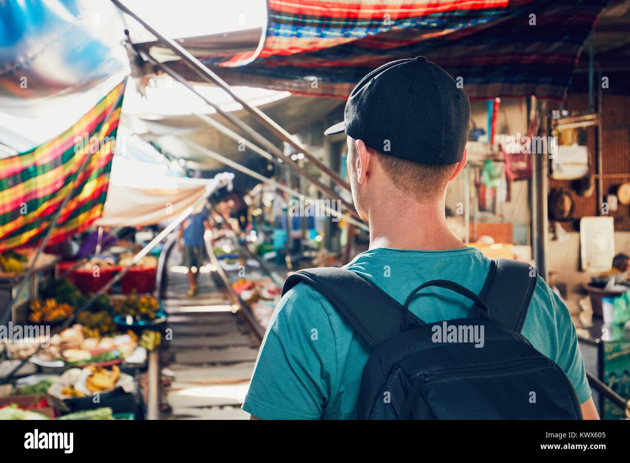 Young man (tourist) walking to open market along the railroad track. Maeklong railway market close to Bangkok in - Stock Image