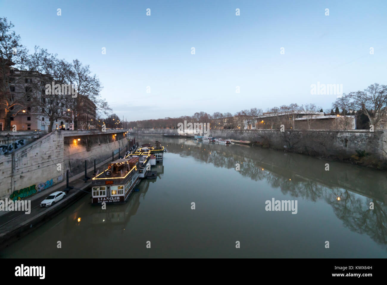 Rome, Italy - December 31, 2017: The Tiber river with some boats moored on the banks of the river, in a panoramic - Stock Image