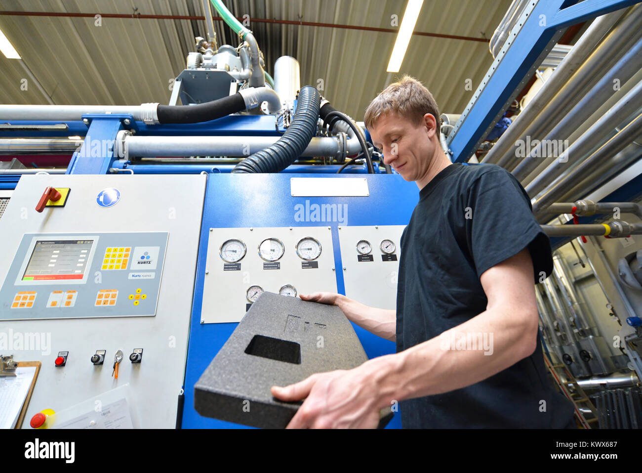 worker operates machine in the plastics industry - production of styrofoam components - Stock Image