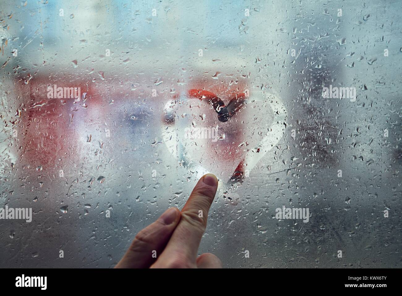 Finger of the young man drawing heart shape on the window with raindrops against city street. - Stock Image