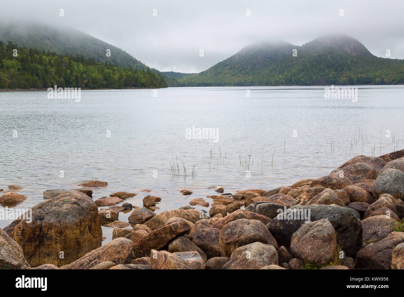 A heavy fog lifting from the calm waters of Jordan Pond on Mount Desert Island. Acadia National Park, Maine - Stock Image
