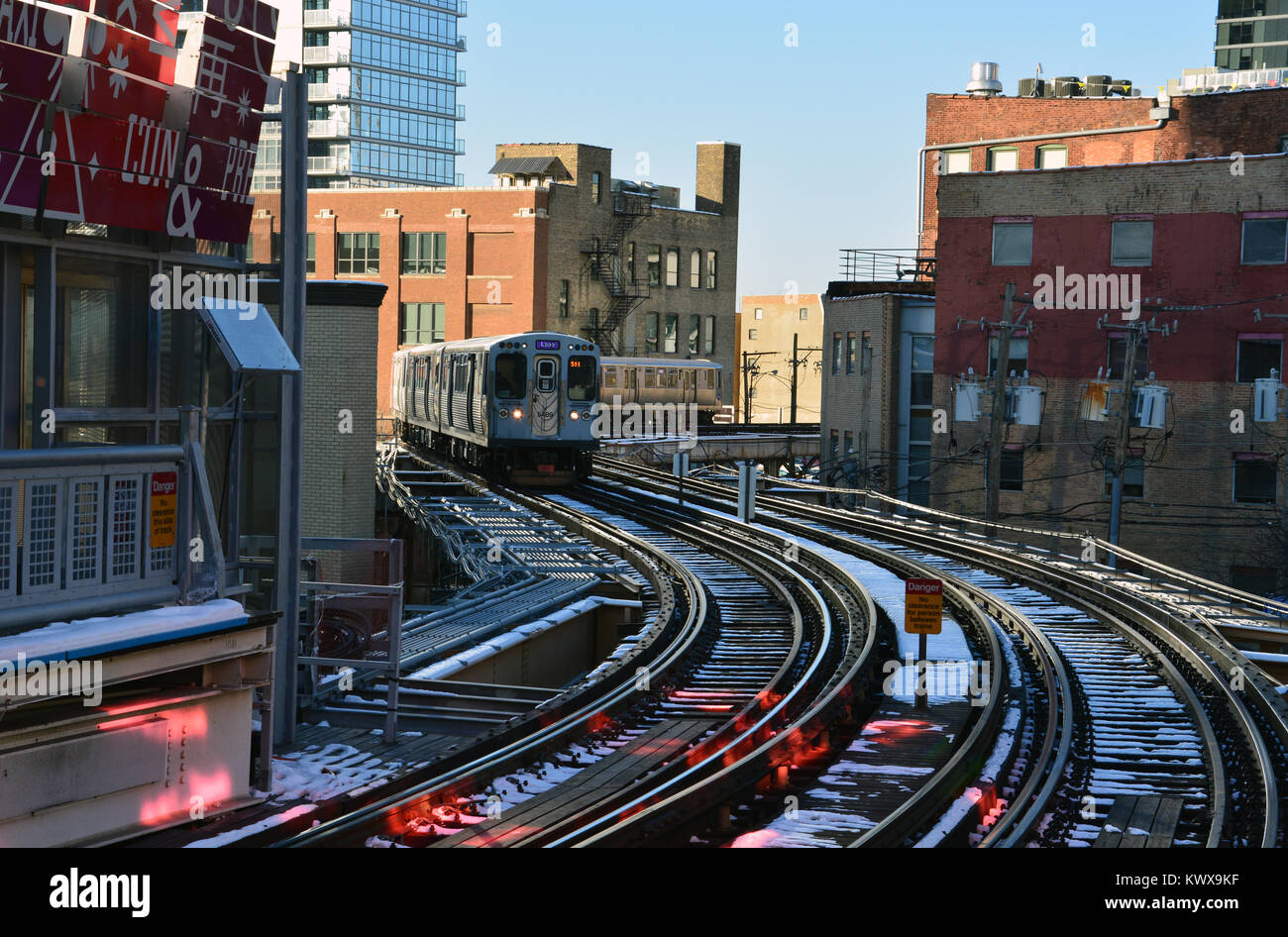 An inbound train rounds the curve to the Chicago Avenue L station on Chicago's Near North Side. - Stock Image