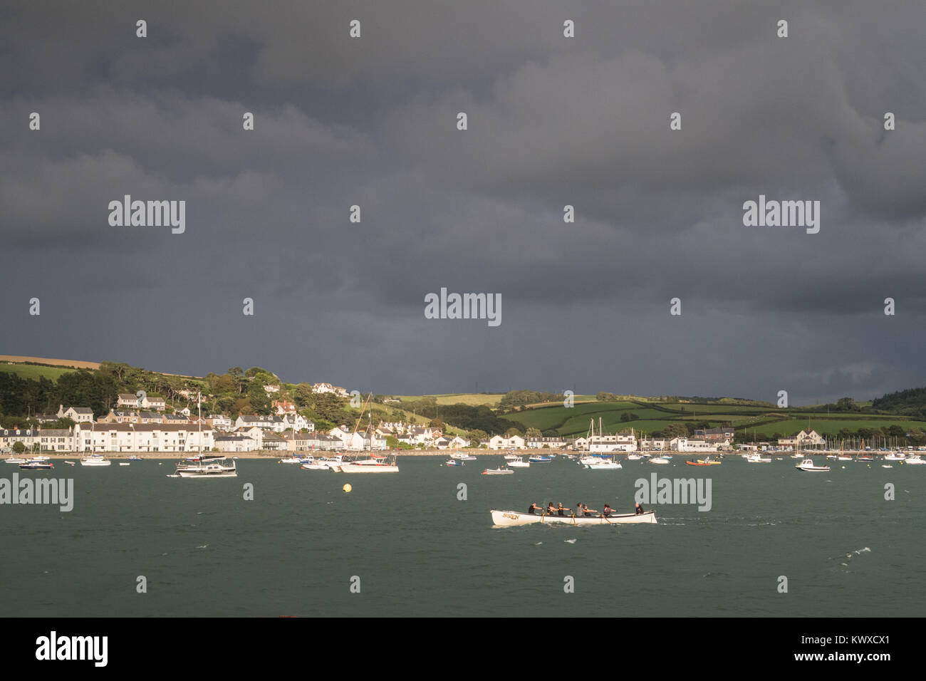 a gig boat rows down the river Torridge in Devon. Instow is in the background. Taken from AppledoreRoy Riley caption - Stock Image