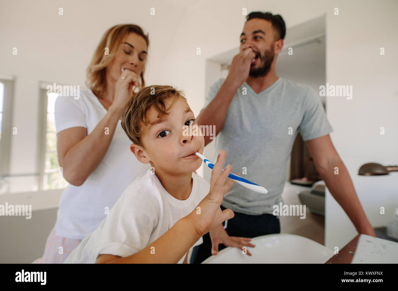 Little boy brushing teeth with his parents in bathroom. Family brushing teeth together in bathroom. - Stock Image