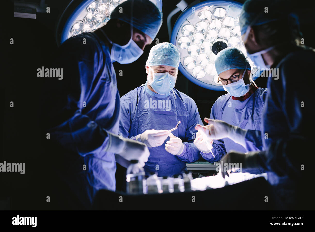 Group of medical professional performing surgery in operation theater. Team of doctors in hospital operating room. - Stock Image