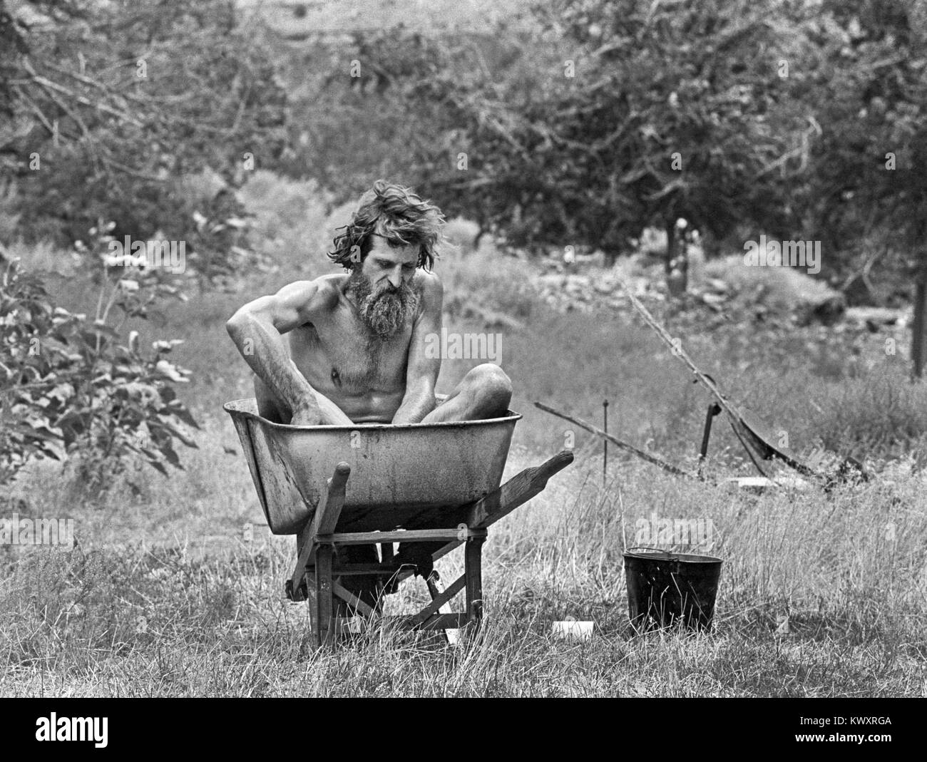 Nik Hougen, an American hermit, bathes in an old wheelbarrow, at his remote residence in Desolation Canyon, Utah, - Stock Image