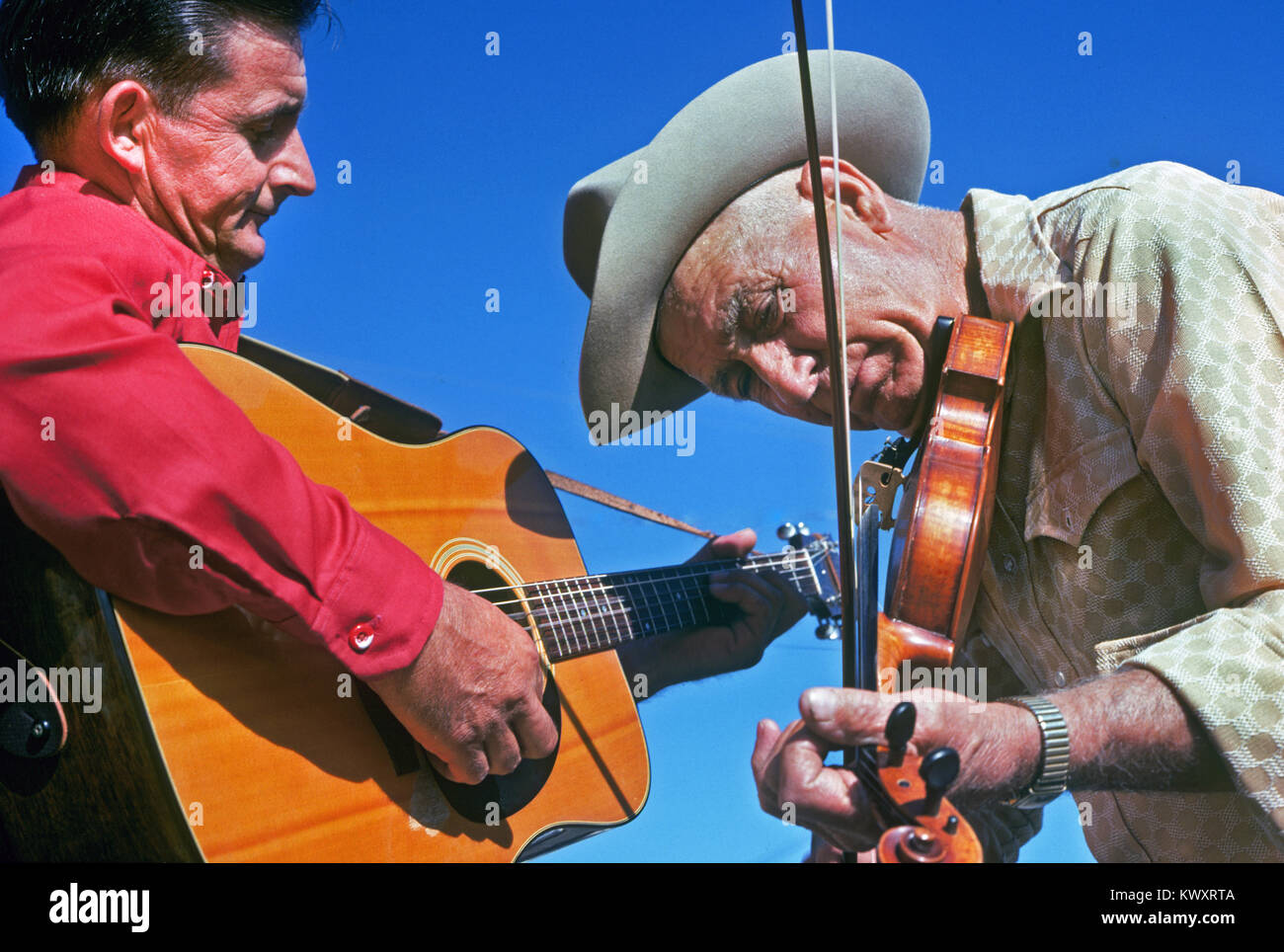A man playing a fiddle or violin and a man playing an acoustic guitar at an old time fiddling contest in Truth or - Stock Image