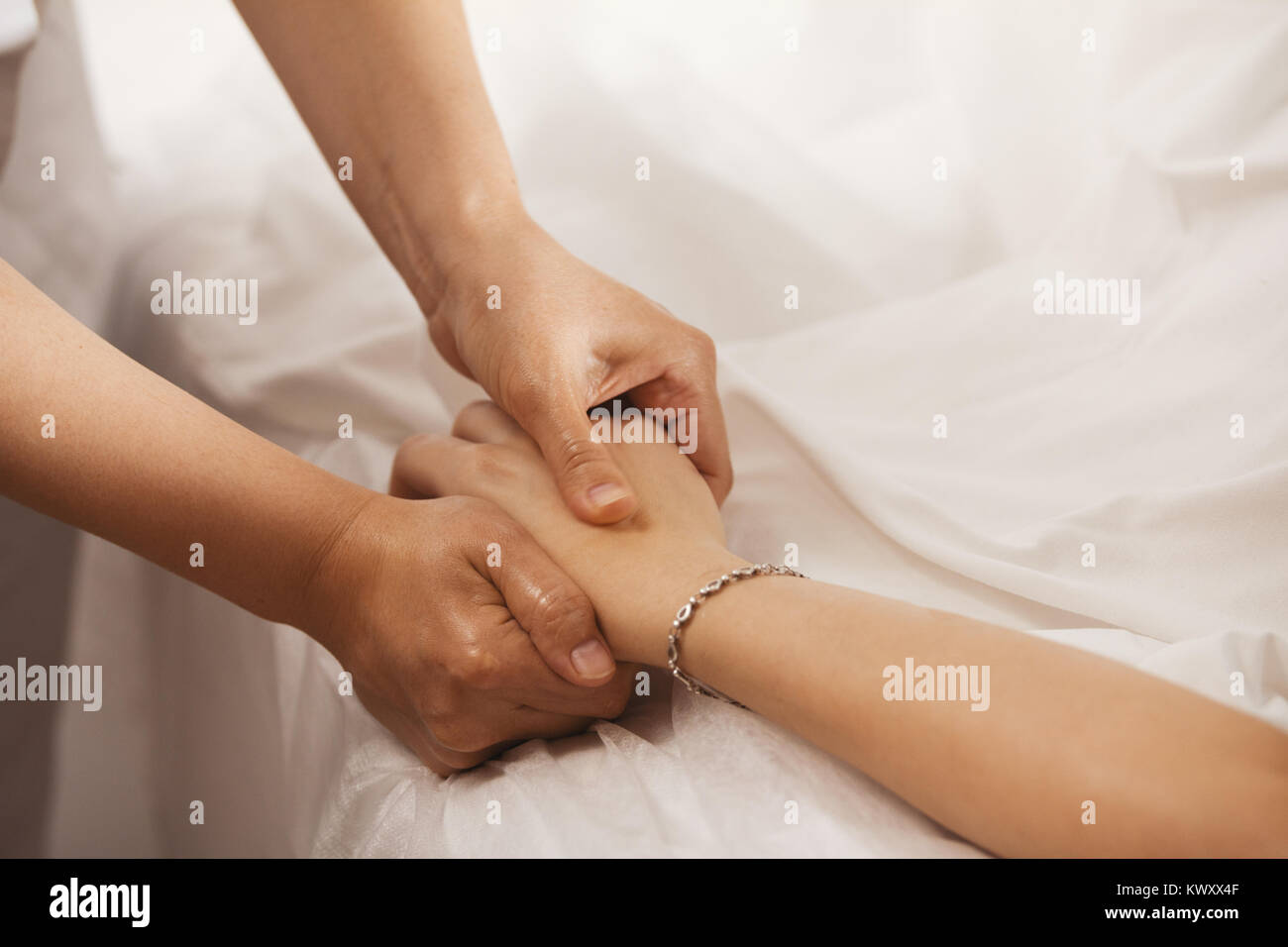 Therapist doing a pressure point massage for woman's hand - Stock Image