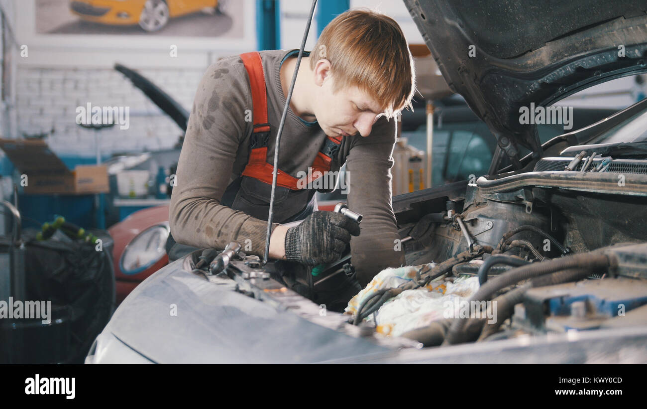 Mechanic checks and repairs automotive engine, car repair, working in the workshop, overhaul, under the hood - Stock Image