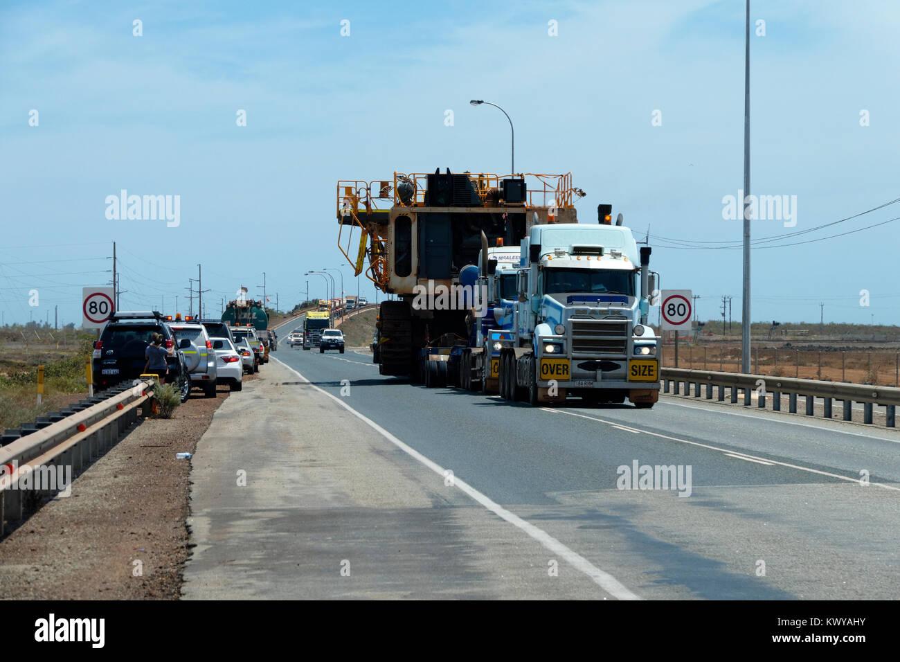 Oversize load being transported by 2 prime mover trucks, Port Hedland, Western Australia - Stock Image