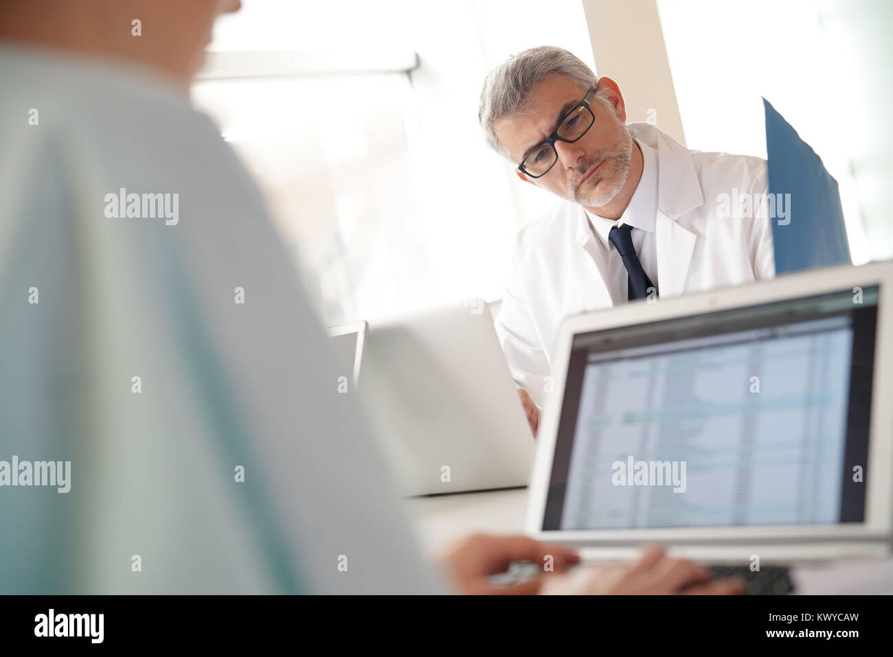 Mature doctor in office working on laptop computer - Stock Image