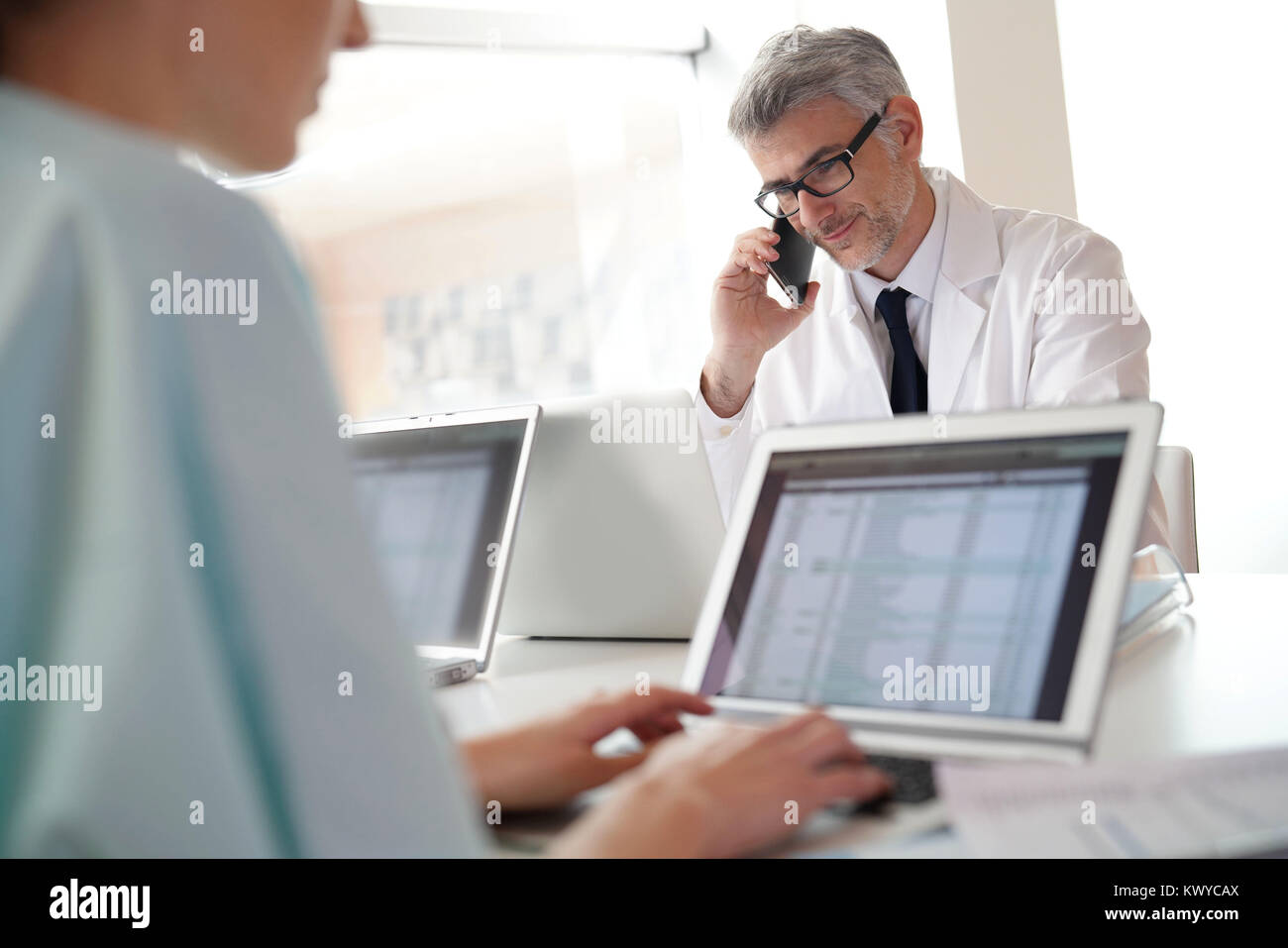 Mature doctor in office talking on phone - Stock Image