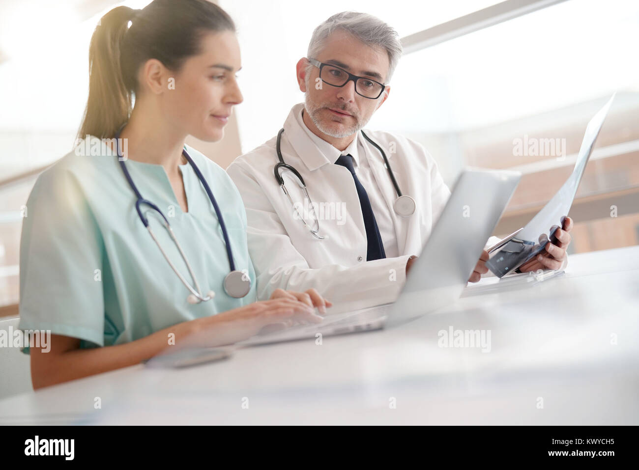 Doctor and nurse in office working on medical report - Stock Image