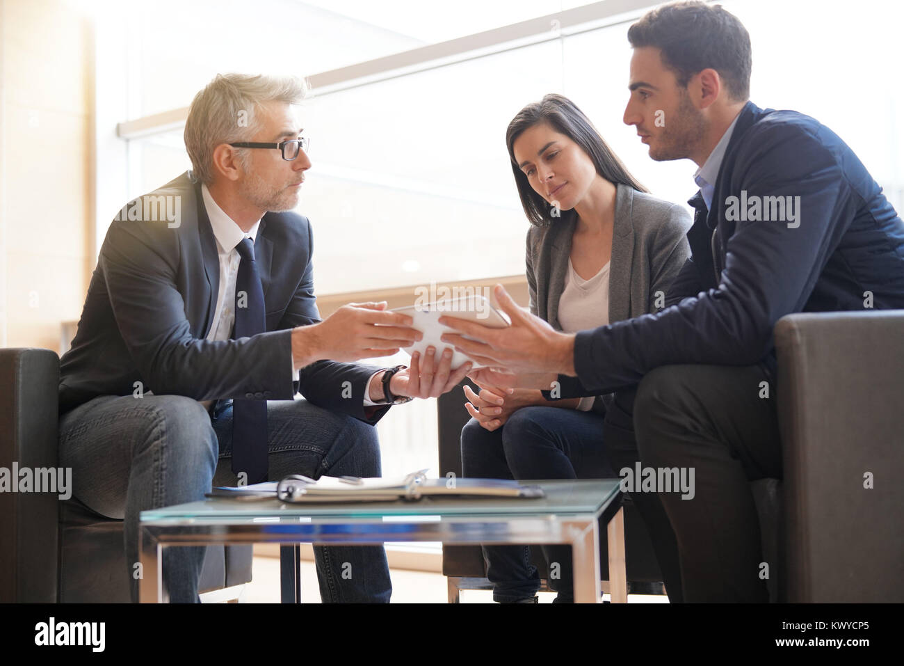 Real-estate agent explaining financial plan to couple buying new home Stock Photo