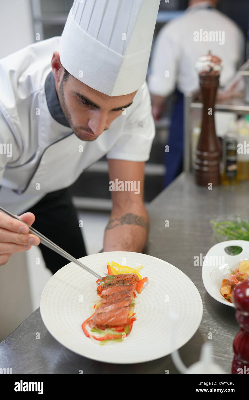 professional cook garnishing plate in restaurant kitchen stock photo