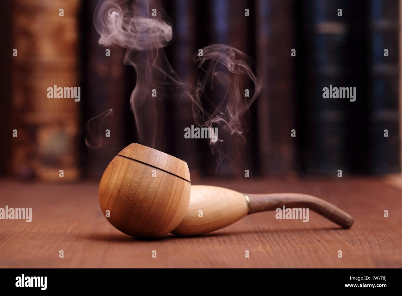 Smoking tobacco pipe on wooden background with old books - Stock Image