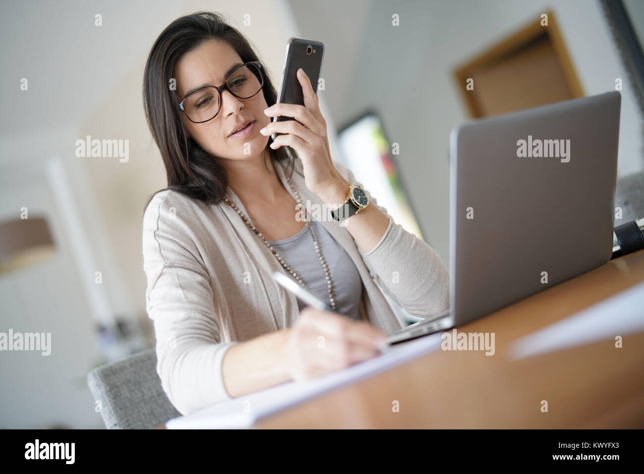 Businesswoman working from home talking on phone - Stock Image