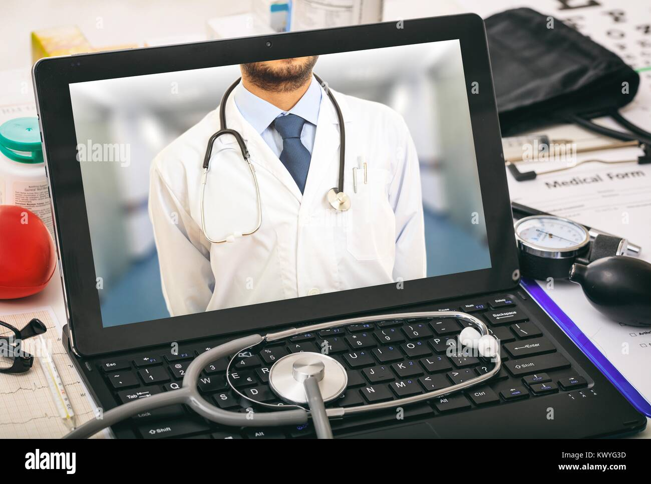 Laptop's screen showing a doctor on a desk - Stock Image