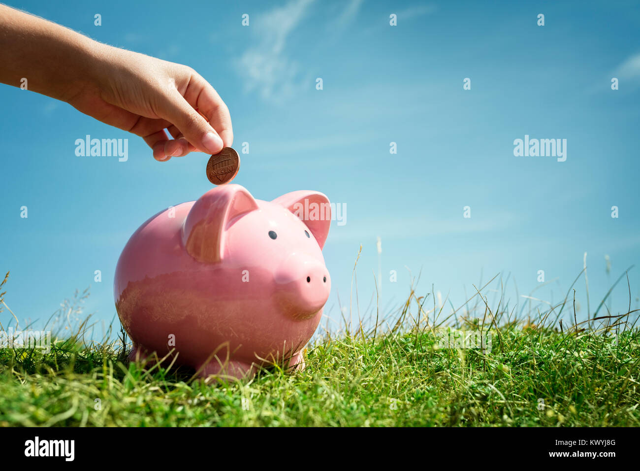 Child hand inserting coin and saving money in piggy bank with grass and blue sky background - Stock Image