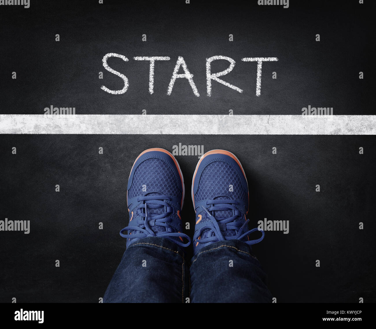 Start line child in sneakers standing next to chalk starting line on blackboard - Stock Image