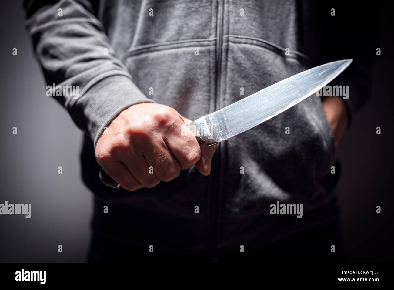 Criminal with knife weapon threatening to stab - Stock Image