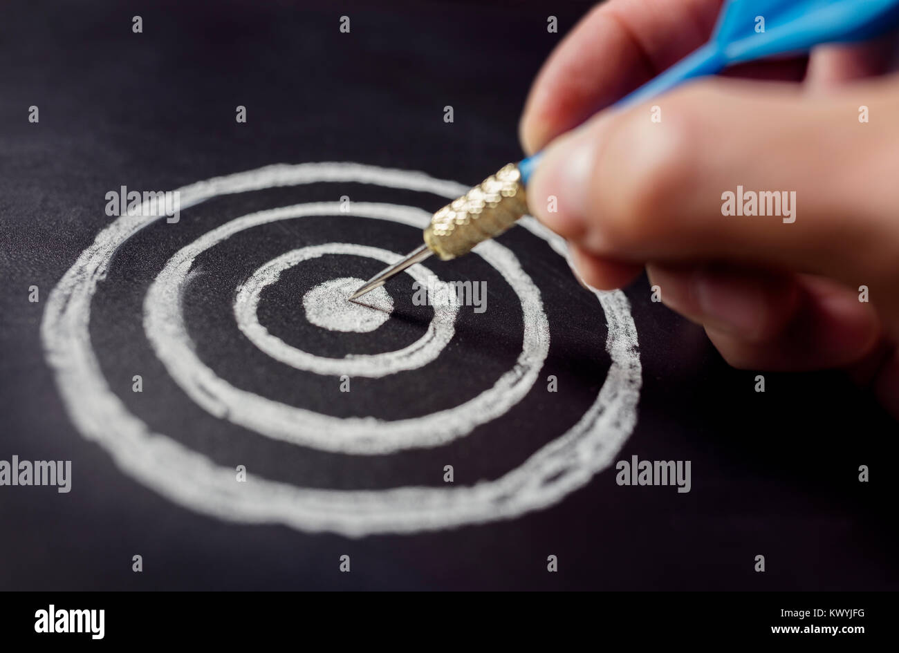 Businessman target for success holding dart on blackboard - Stock Image