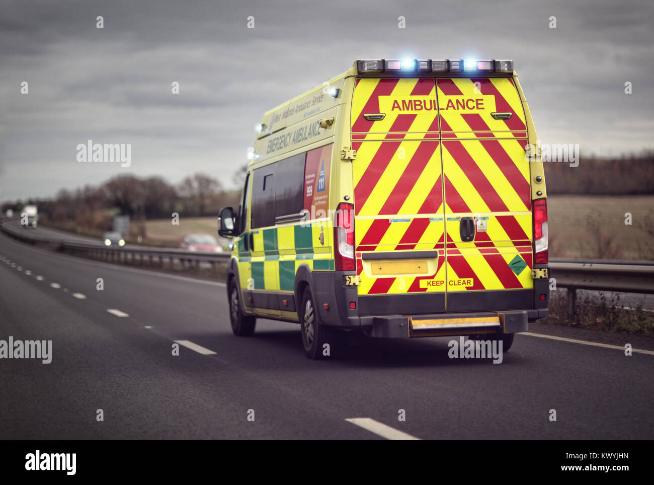 British ambulance responding to an emergency in hazardous bad weather driving conditions on a UK motorway - Stock Image