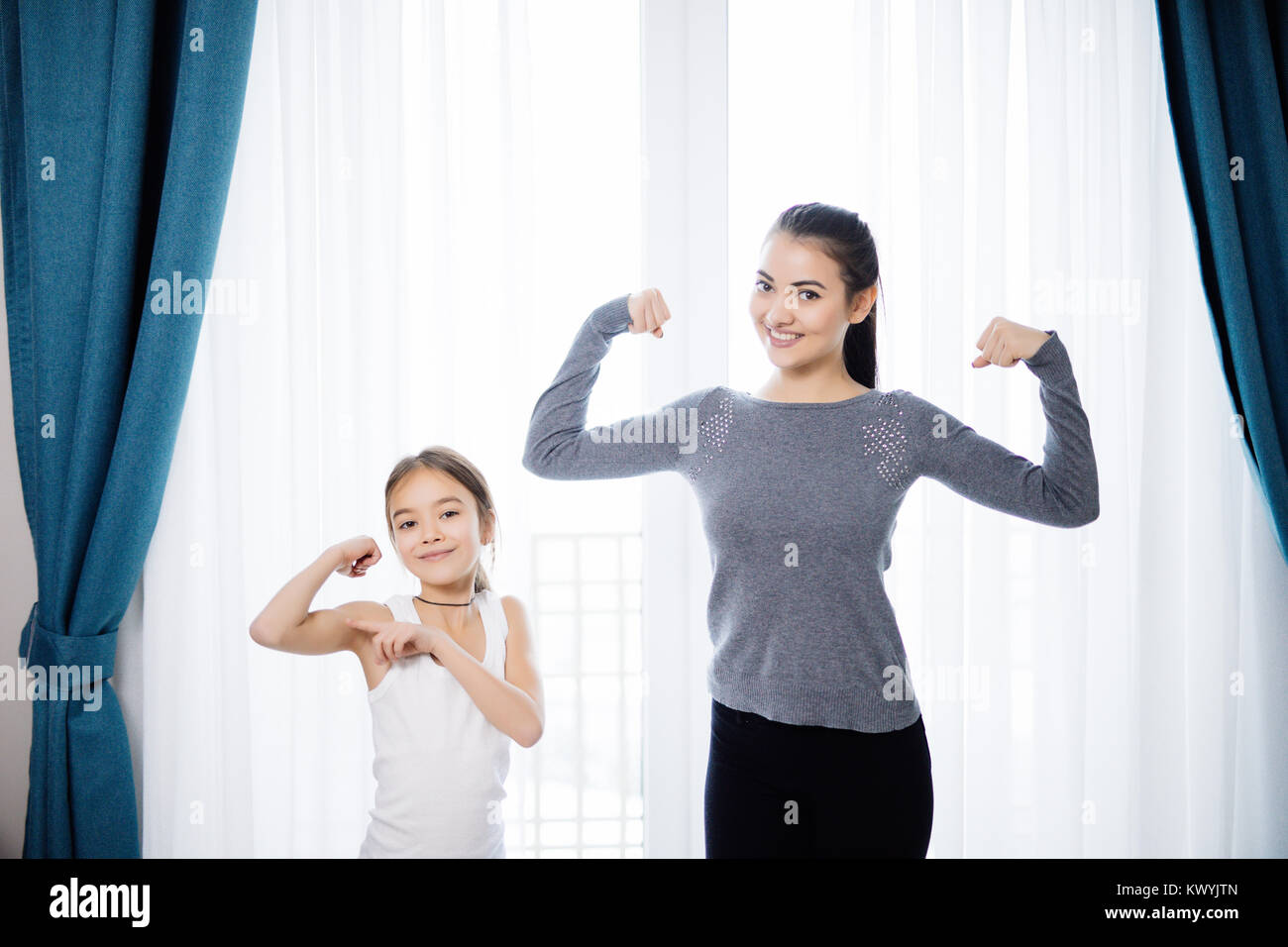 Young woman and charming little daughter are showing their biceps and smiling while working out at home - Stock Image