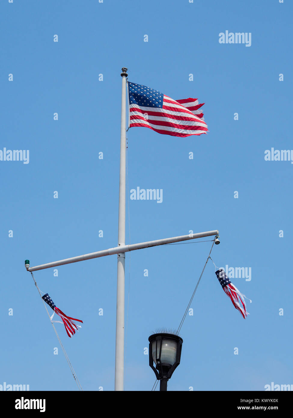 The American flag is flying on top of a flagpole at the port city of Monterey, California - Stock Image