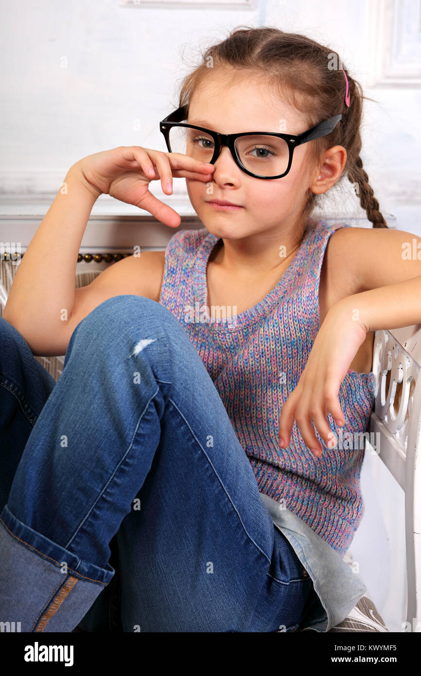 a0c9d9ec1 Serious emotional calm kid girl in eyeglasses looking and thinking about in blue  jeans on the