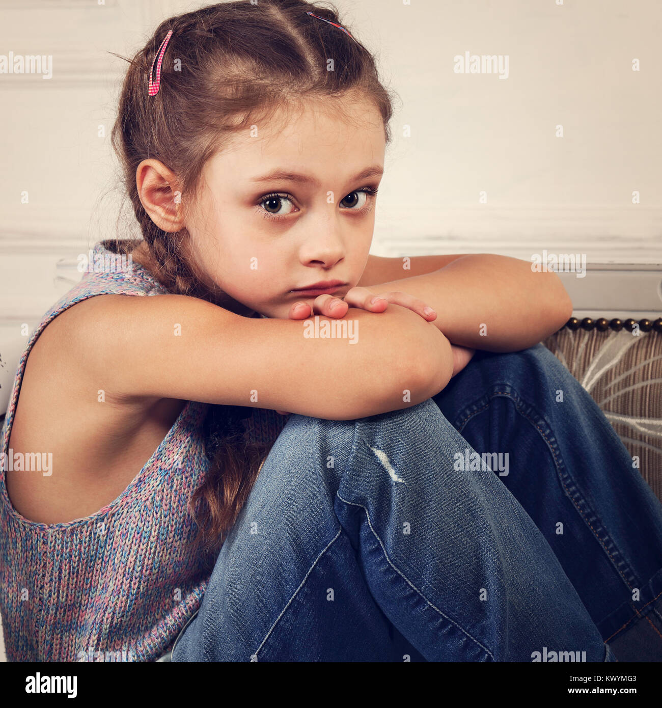 5af5292cc Sad thinking and dreaming kid girl sitting on the bench in blue jeans and  blouse and