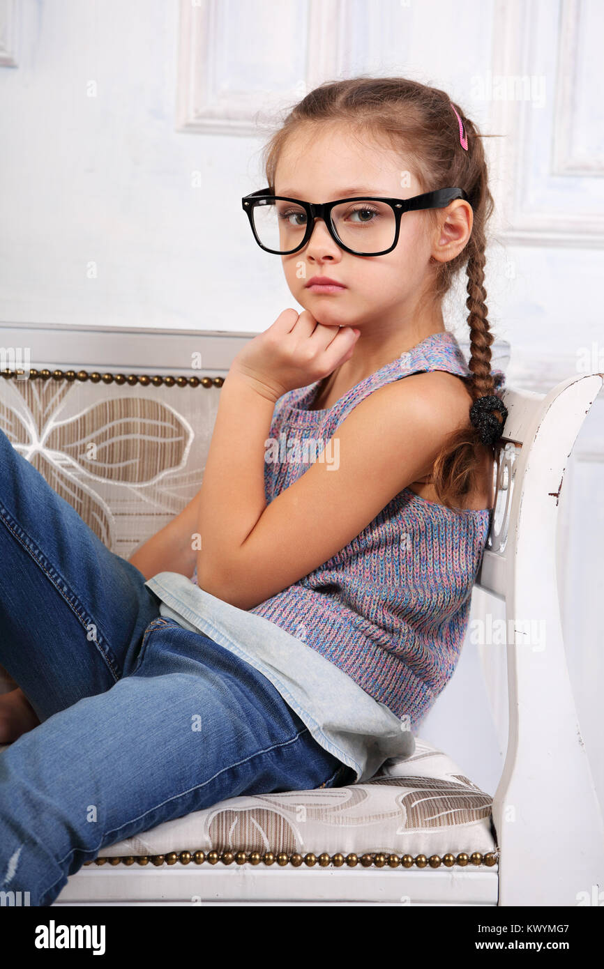 83212e999 Serious calm kid girl in eyeglasses looking and thinking about with fun  face in blue jeans