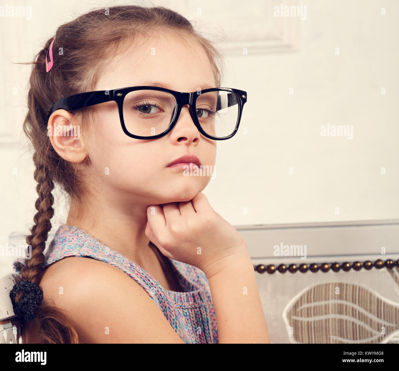 66df31ca5a Happy serious calm kid girl in eyeglasses looking and thinking about with  fun face. Closeup toned portrait