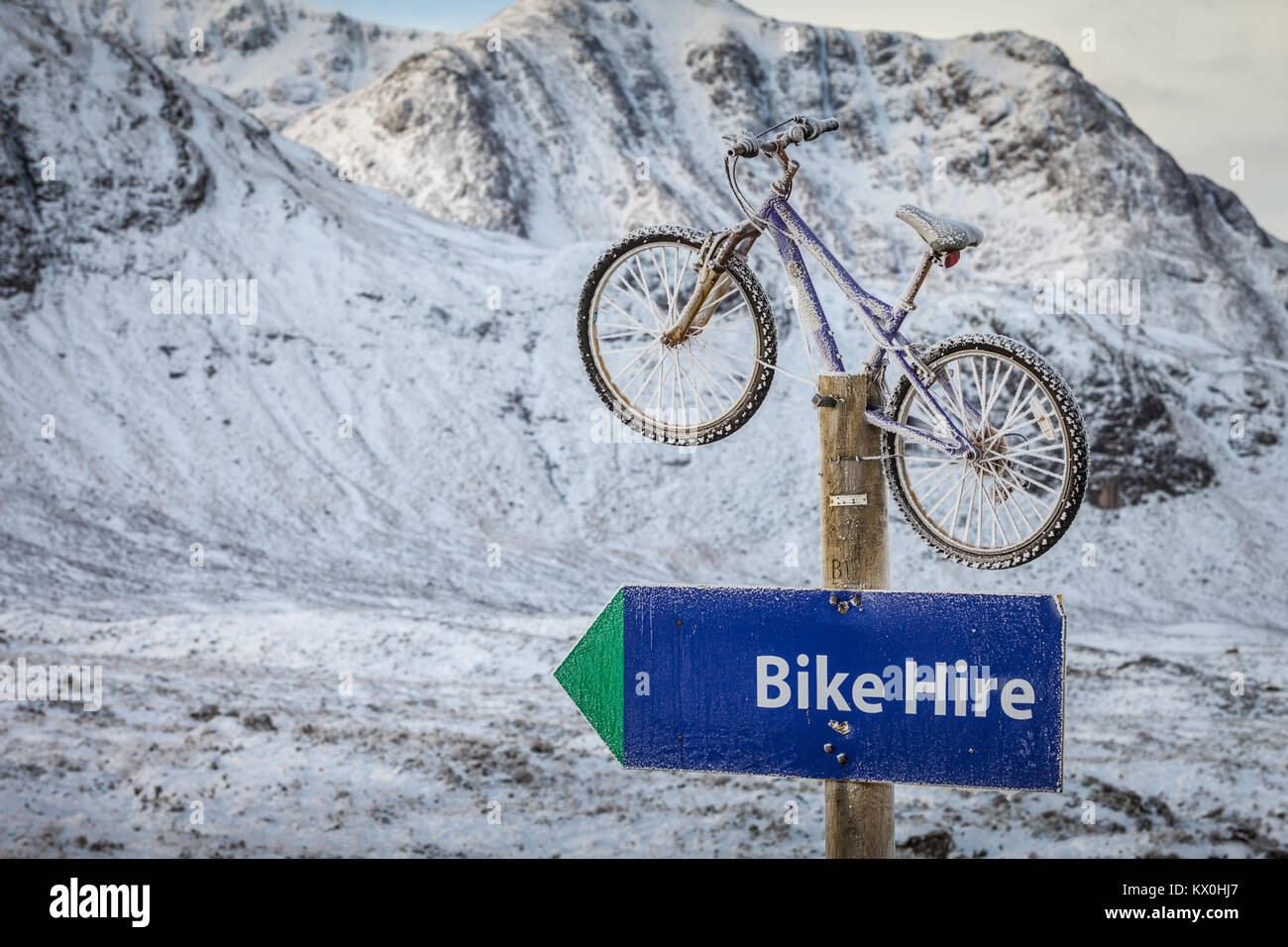 Bike or bicycle on a post advertising cycle hire, Glencoe, Scotland UK Stock Photo