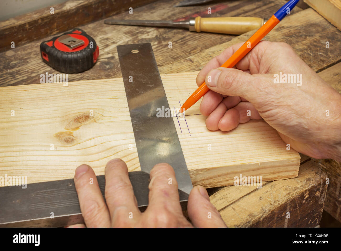 Woodworker draws a line on a wooden board, putting it on a workbench - Stock Image