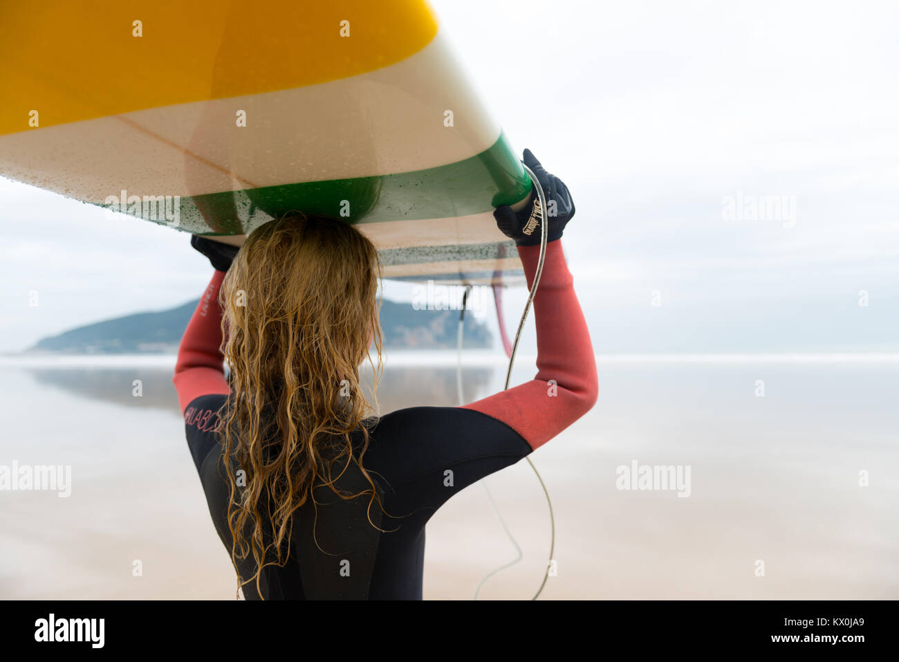 Surfer woman looking at the sea while holding surfboard - Stock Image