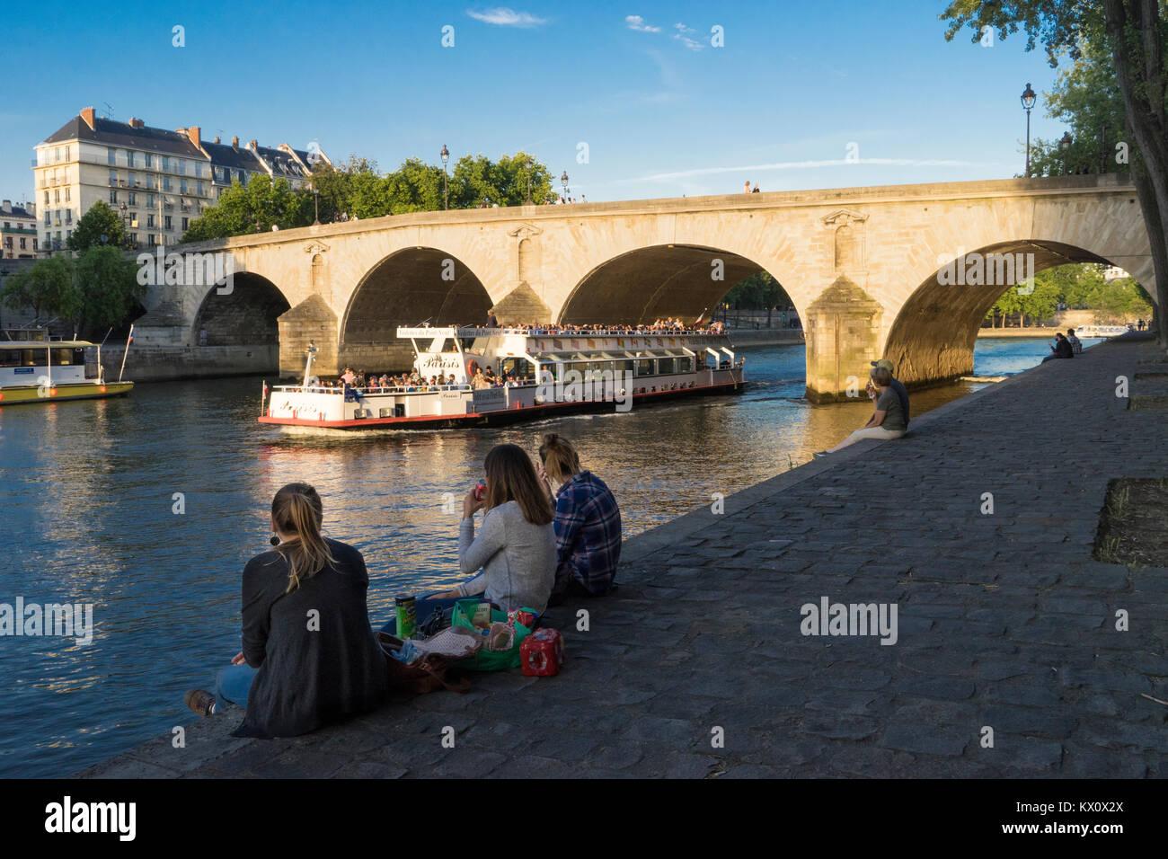 France, Paris (75), Woman picnicking on the Quai de Bourbon with the  Pont Marie behind - Stock Image