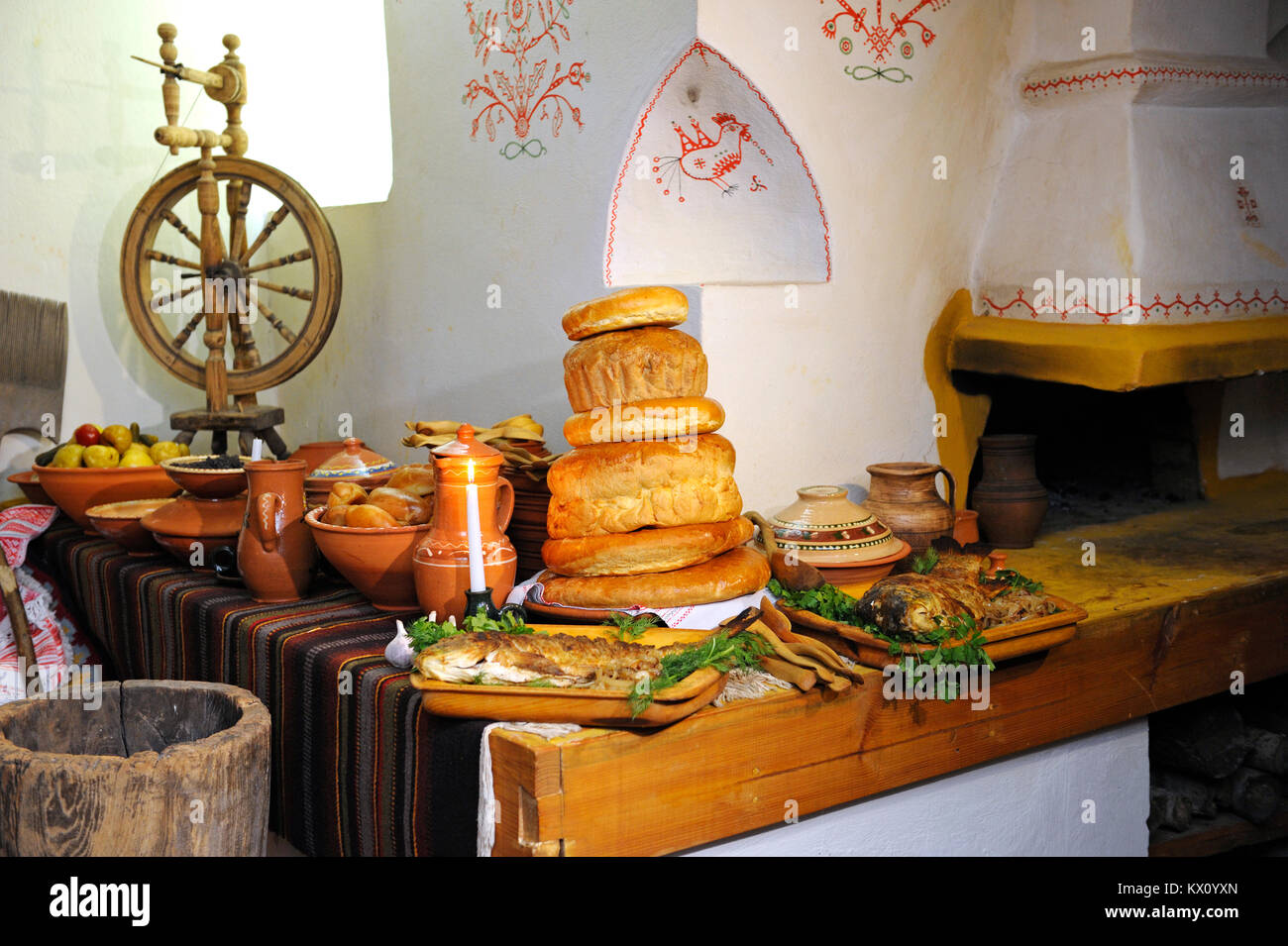 """Traditional Ukrainian food on Christmas Eve: ewer with """"kutia"""", fried fish, garlic and bread placed near stove. Stock Photo"""