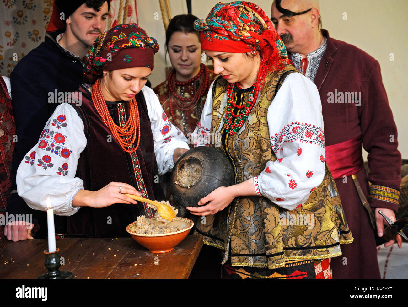 "People in native dresses prepare traditional dish ""kutia"" on Christmas Eve. Reconstruction of Ukrainian folk traditions. - Stock Image"