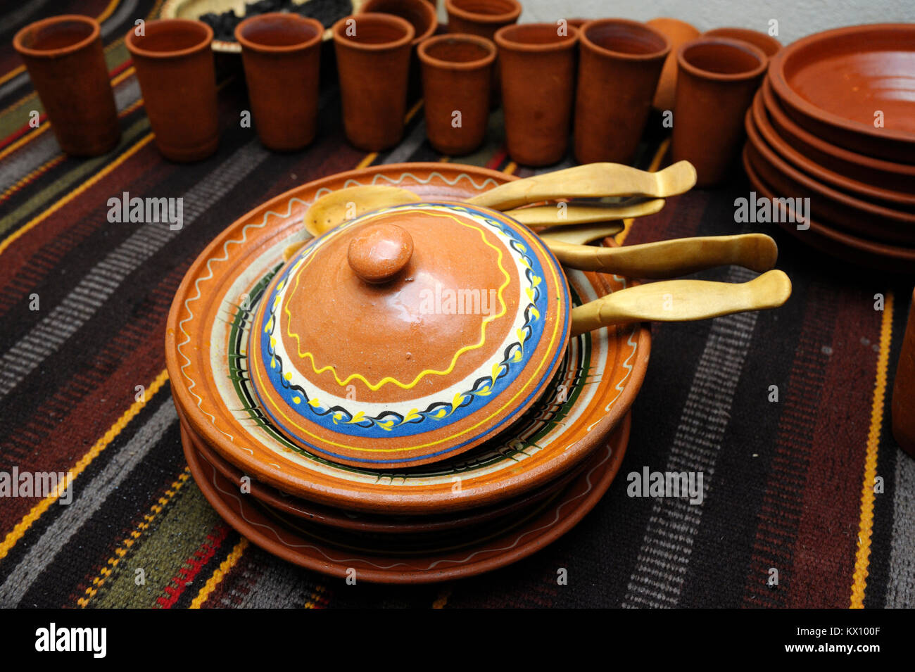 Traditional Ukrainian tableware – plates, wooden spoons and clay cups - placed on a bench. January 4,2018. Kiev, Stock Photo