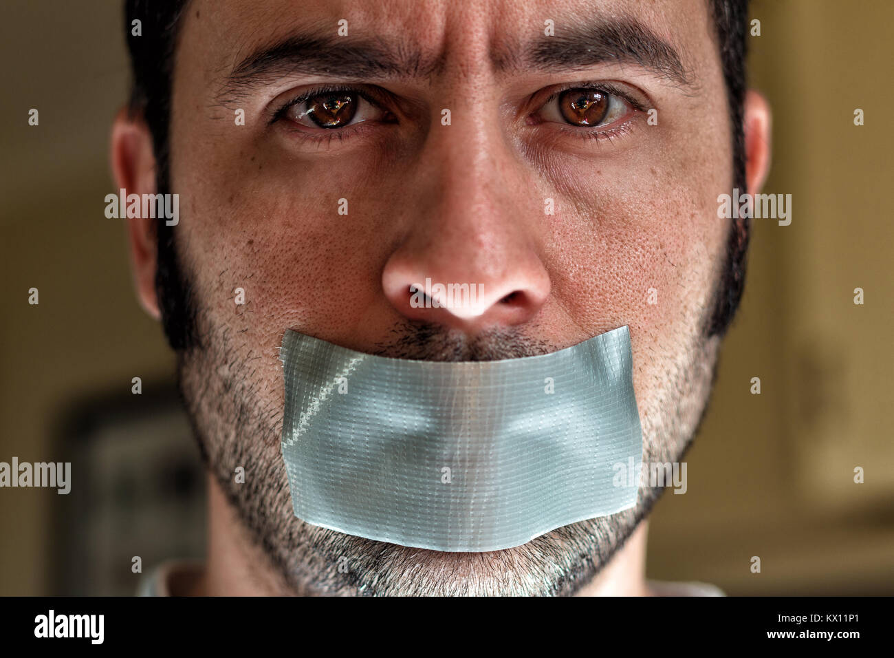 Close up portrait of a man with duct tape over his mouth - Stock Image