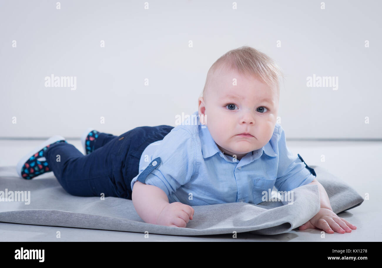 ba1921fd6948 Cute little baby boy in blue shirt and jeans lying on the blanked and  posing in the photo studio on white background