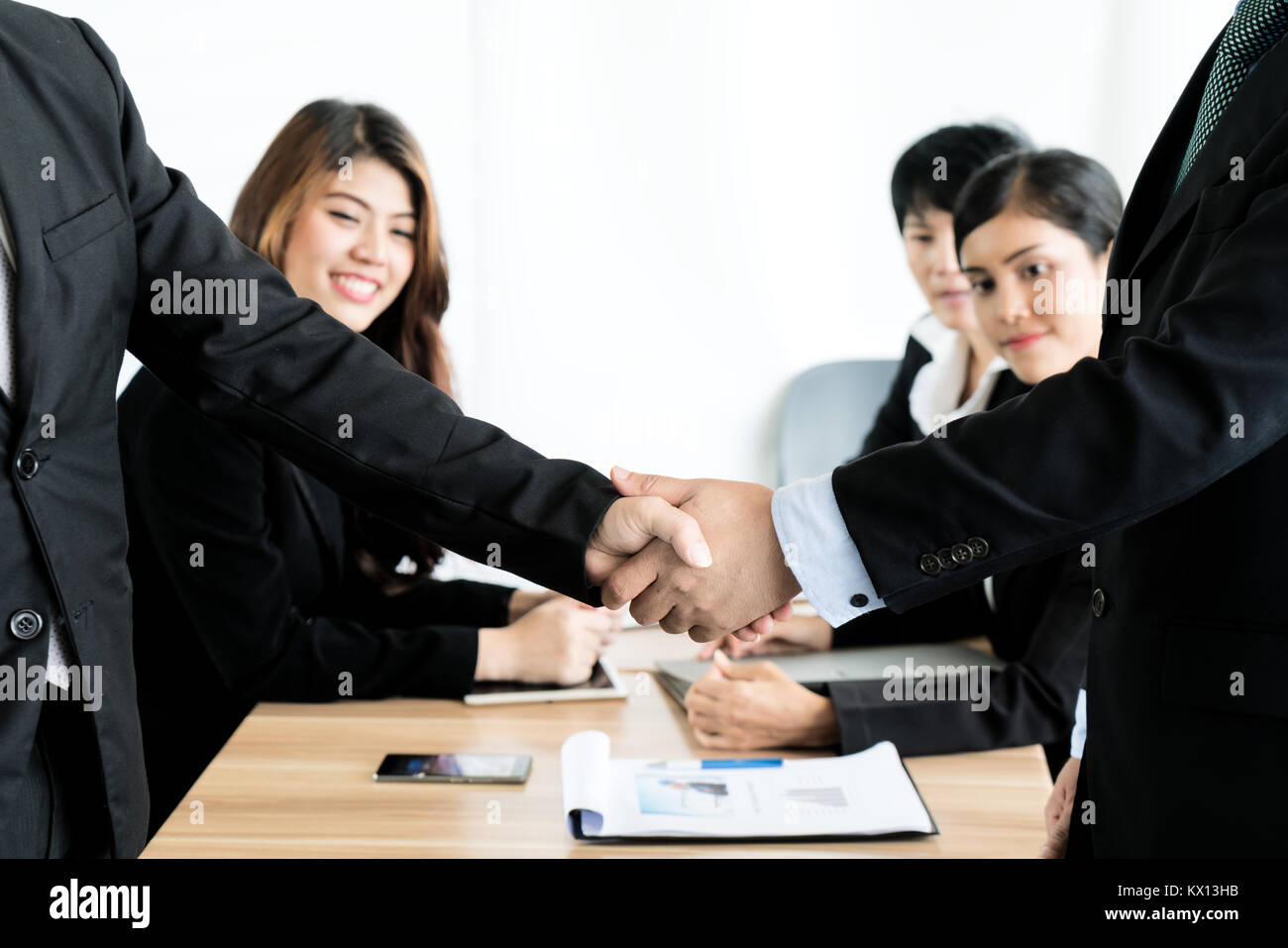 Asian businessman shaking hands in conference room. Business people shaking hands agreement concept. - Stock Image