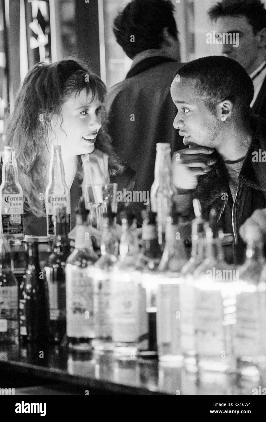 Young mixed race couple enjoying a special moment on a night out in a club in London, 1980s, - Stock Image