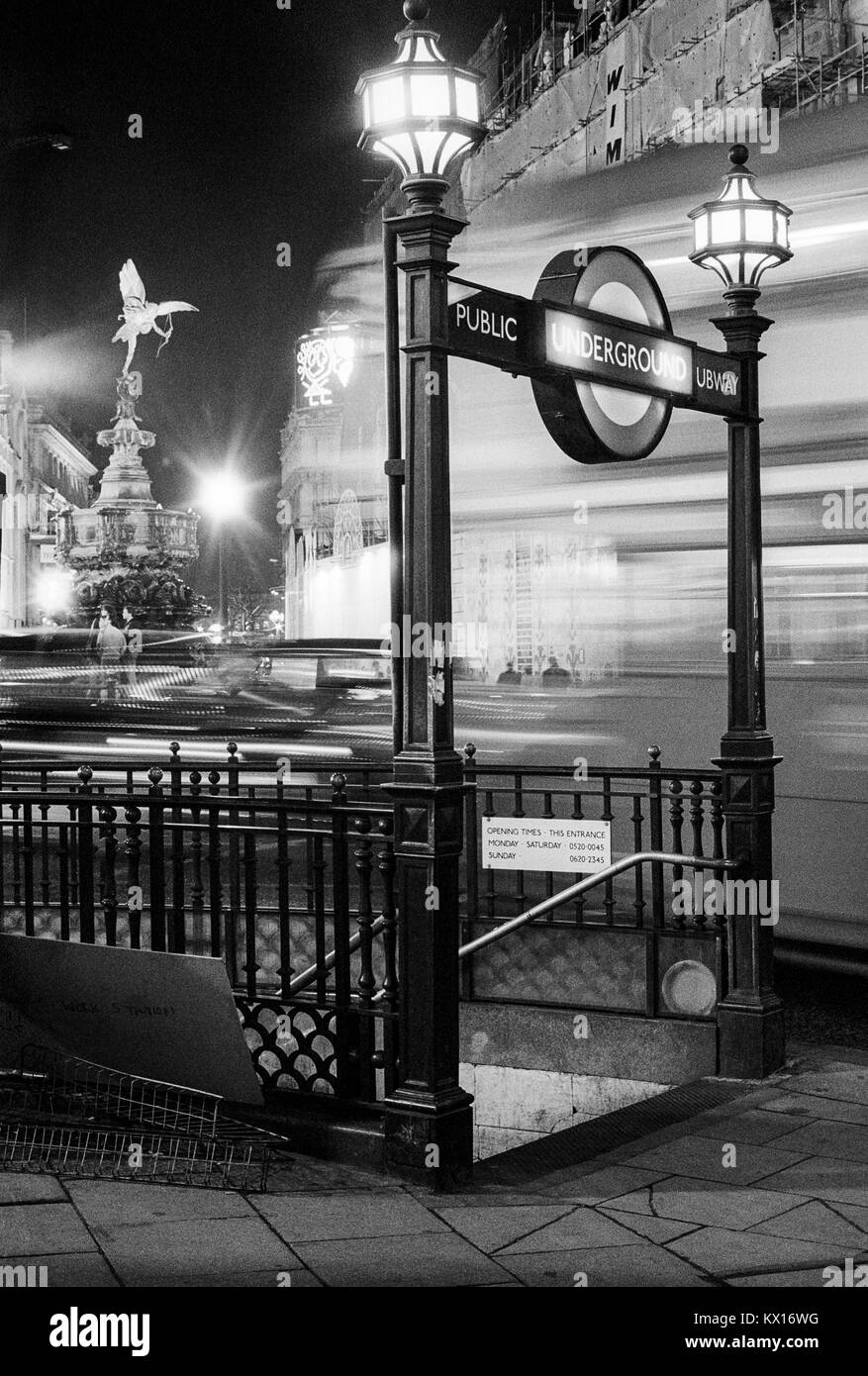 Public subway underground entrance at Piccadilly Circus with london Transport bus passing and Eros statue, at night, - Stock Image