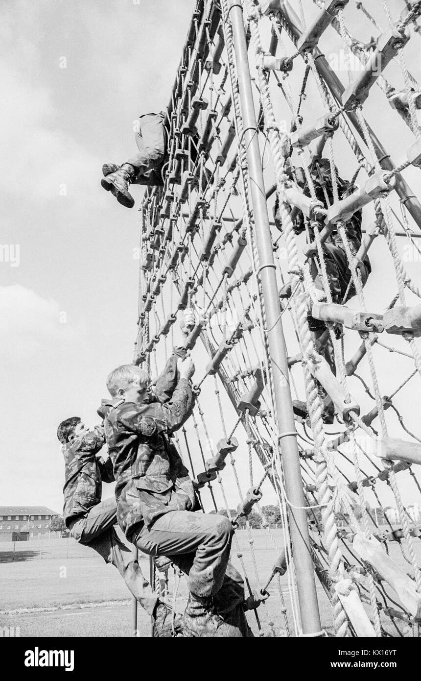 British army squaddies undergoing basic training climb over rope netting as part of an obstacle course, 15th June - Stock Image