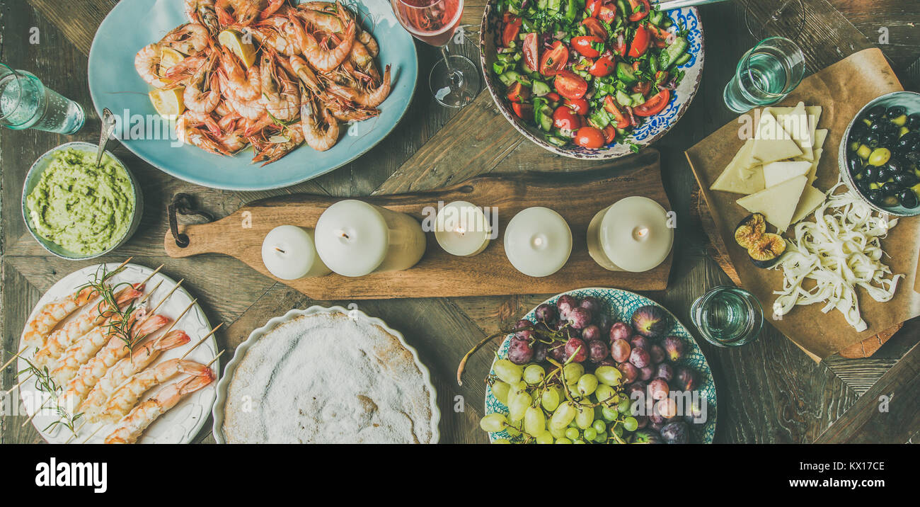 Flat-lay of salad, shrimps, olive, grape, cake, wide composition - Stock Image