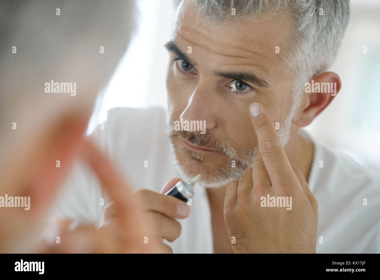 Portrait of middle-aged man applying eye concealer - Stock Image