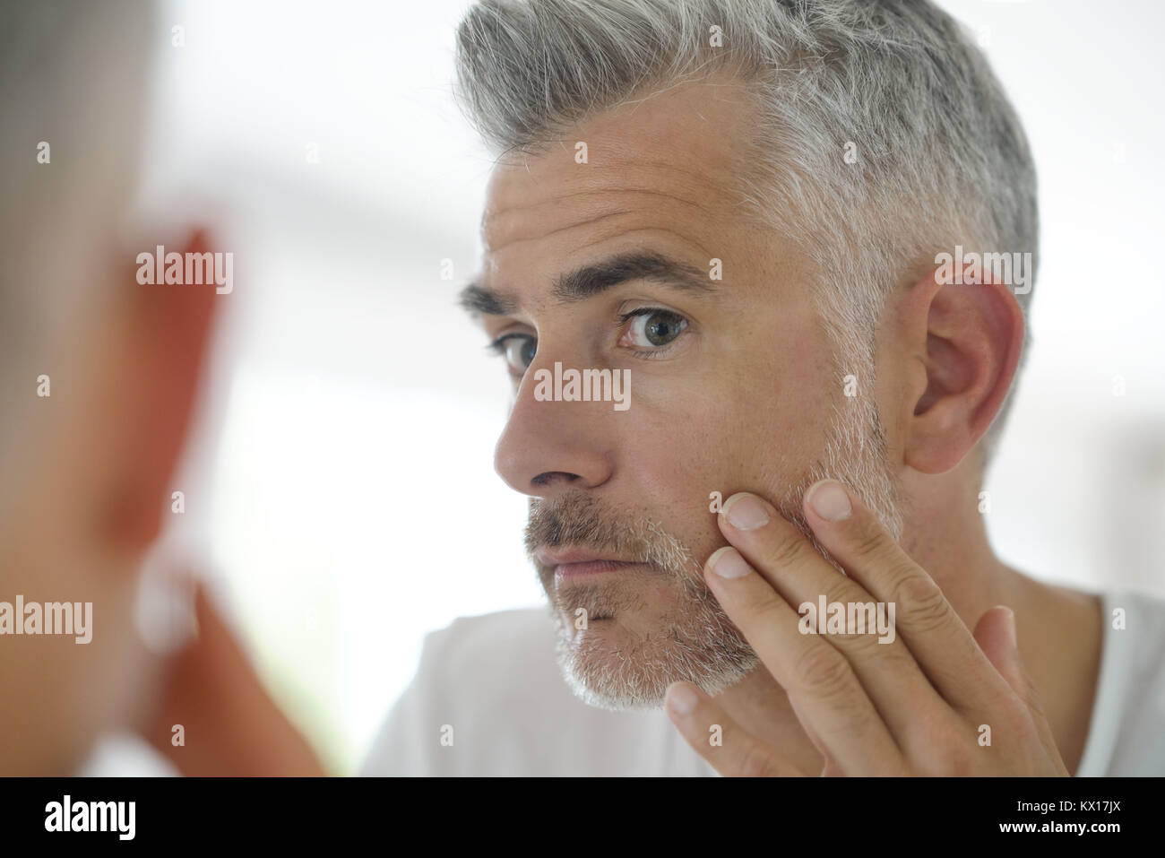 Middle-aged man applying cosmetic on his face, mirror view - Stock Image