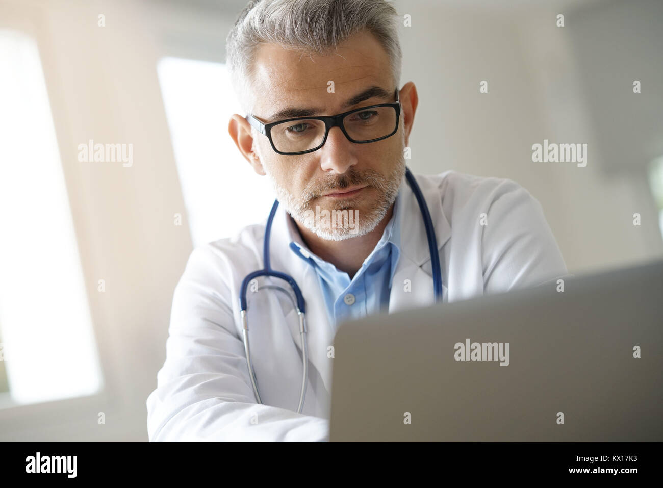 Doctor in office working on patient file Stock Photo